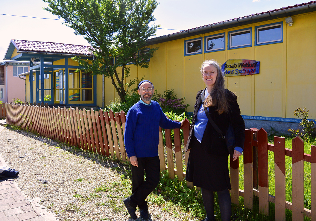 Image of Terran and Jutta in front of the Scoala Waldorf Hans Spalinger in Roşia, Romania
