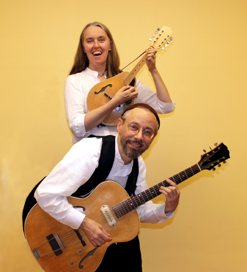 Vertical photo of Jutta & the Hi-Dukes (tm) as a duet – Jutta Distler, standing in back – mandolin, Terran Doehrer, in front – guitar. Photo by Betina Distler. Photo copyright 2012 Modal Music, Inc. (tm). All rights reserved.