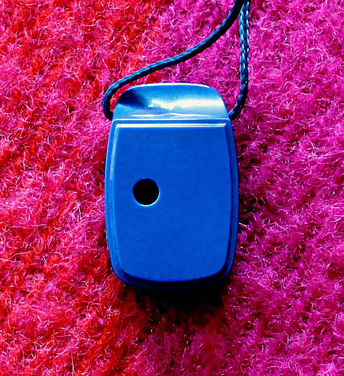 Back of a blue ocarina showing the thumb hole, laying on a red wool background.
