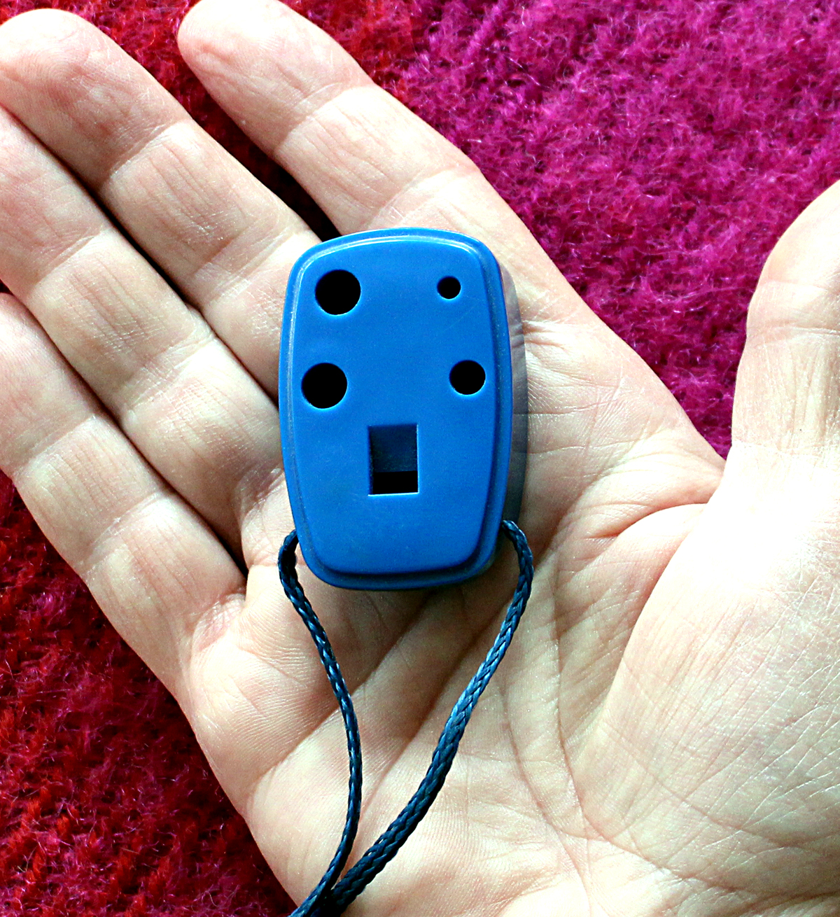Blue ocarina laying in the palm of a hand.